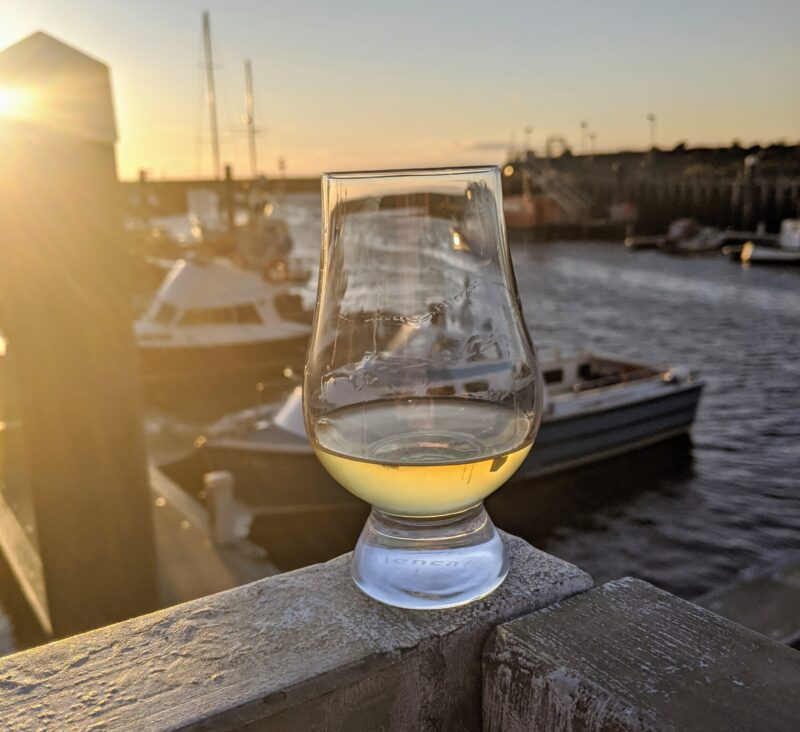 A glencairn of whisky sitting by the sea